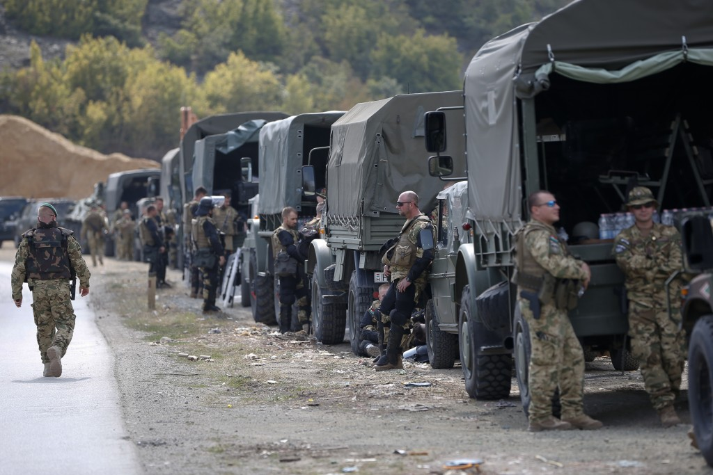 In this photo taken on Sept. 9, 2018, soldiers of NATO-led peacekeeping force KFOR take a break by the side of the road in the village of Kosterc, Kos