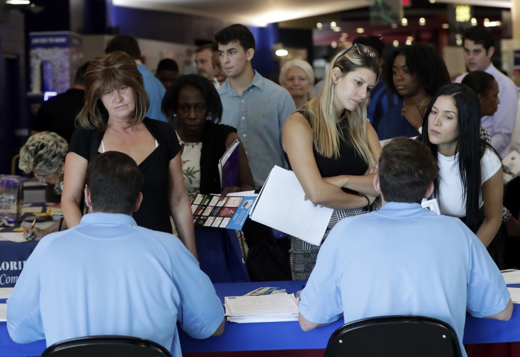 FILE- In this June 21, 2018 file photo, job applicants talks with representatives from Aldi at a job fair hosted by Job News South Florida, in Sunrise
