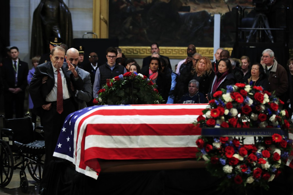Former Sen. Bob Dole salutes the flag-draped casket containing the remains of former President George H.W. Bush as he lies in state at the U.S. Capito