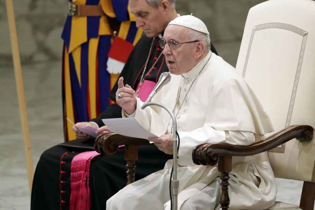 Pope Francis, flanked by Vatican Prefect of the Pontifical Household, Archbishop Georg Ganswein, delivers his message during a weekly general audience