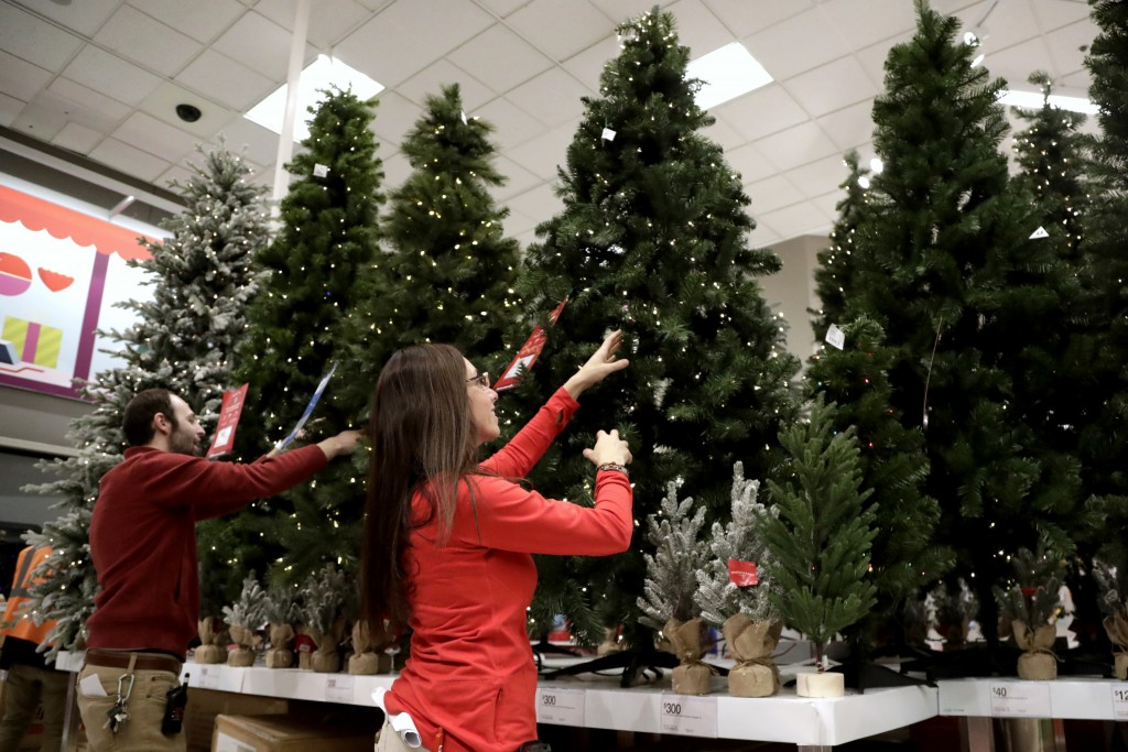 FILE- In this Friday, Nov. 16, 2018, file photo, employees work on the presentation of Christmas trees at a Target store in Bridgewater, N.J. On Thurs