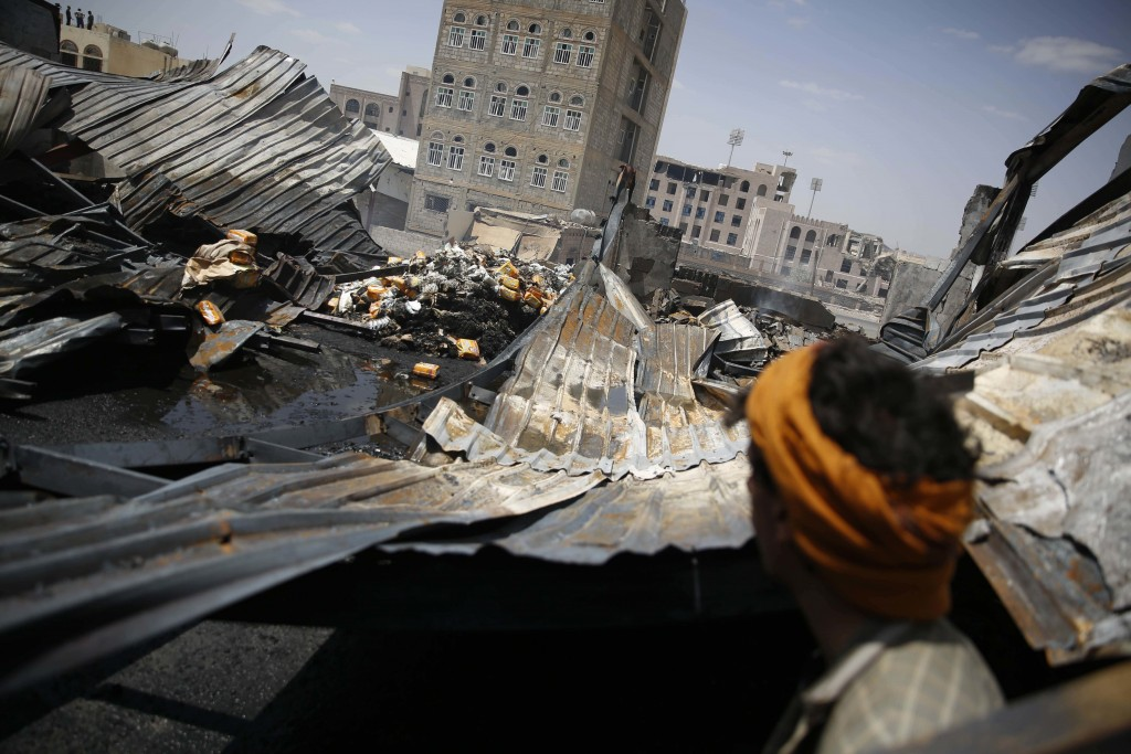 FILE - In this Thursday, Sept. 17, 2015, file photo, a worker looks at a chocolate factory destroyed by a Saudi-led airstrike in Sanaa, Yemen. Envoys