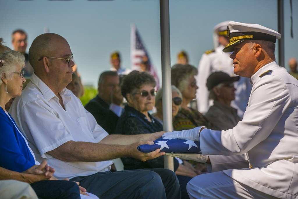 FILE - In this July 7, 2018 file photo, U.S. Navy Rear Admiral John Krietz presents a folded American flag to Mark Arickx, nephew to Seaman First Clas