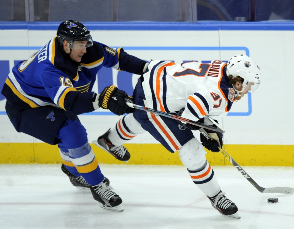 St. Louis Blues' Jay Bouwmeester (19) reaches for the puck with Edmonton Oilers' Connor McDavid (97) during the second period of an NHL hockey game, W