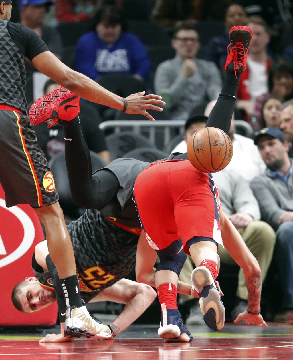 Atlanta Hawks center Alex Len (25) falls over Washington Wizards guard Austin Rivers (1) during the first half of an NBA basketball game Wednesday, De