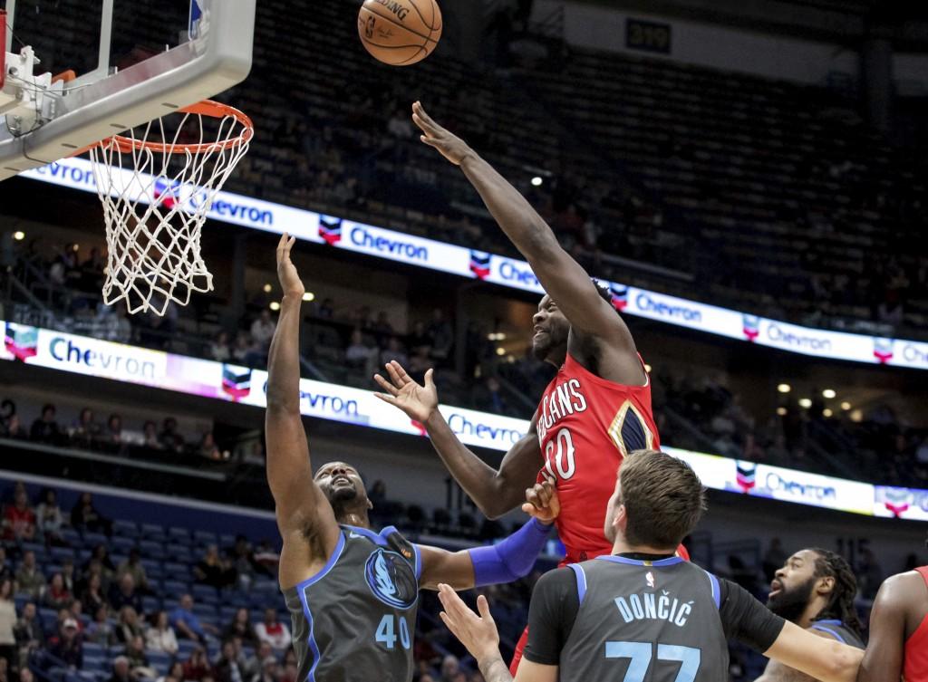 New Orleans Pelicans forward Julius Randle (30) shoots over Dallas Mavericks forward Harrison Barnes (40) and forward Luka Doncic (77) in the first ha