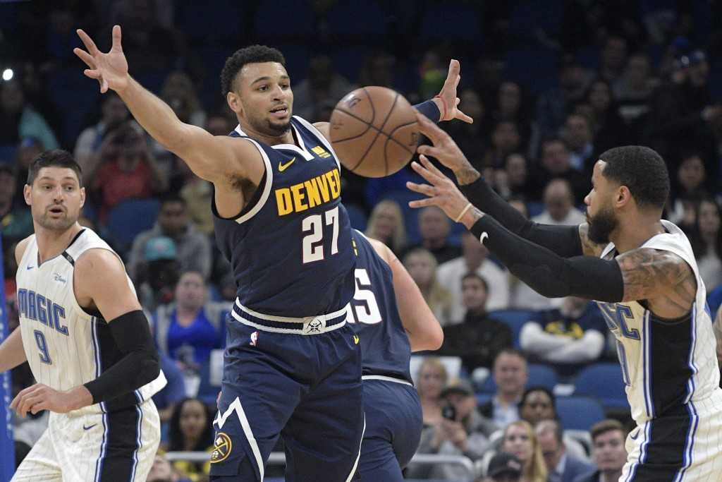 Denver Nuggets guard Jamal Murray (27) defends a pass between Orlando Magic center Nikola Vucevic (9) and guard D.J. Augustin, right, during the first