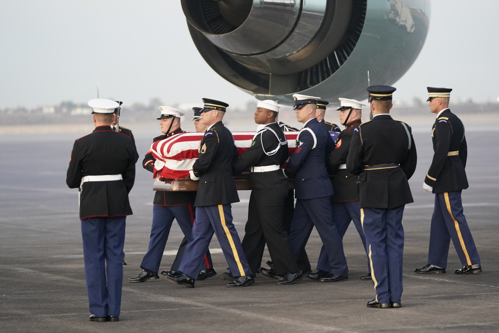 The flag-draped casket of former President George H.W. Bush is carried by a joint services military honor guard Wednesday, Dec. 5, 2018, at Ellington