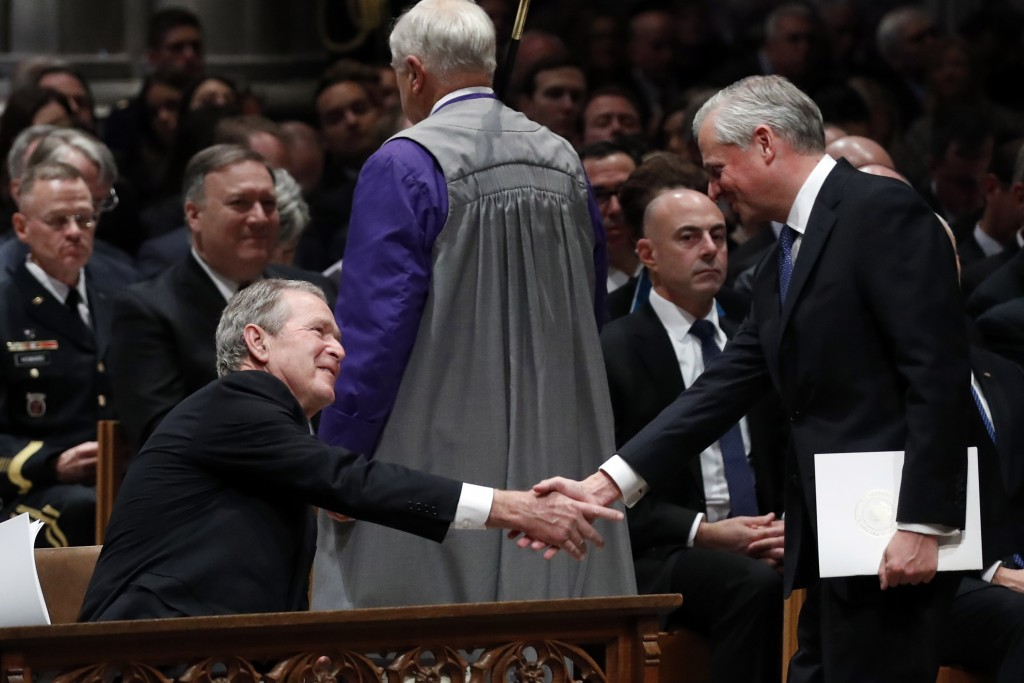 Presidential biographer Jon Meacham, shakes hands with former President George Bush after speaking during the State Funeral for former President Georg