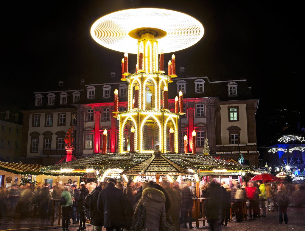 In this Tuesday, Dec. 4, 2018 photo people pay a visit to the traditional Christmas market with a turning pyramid in Heidelberg, Germany. The Christma