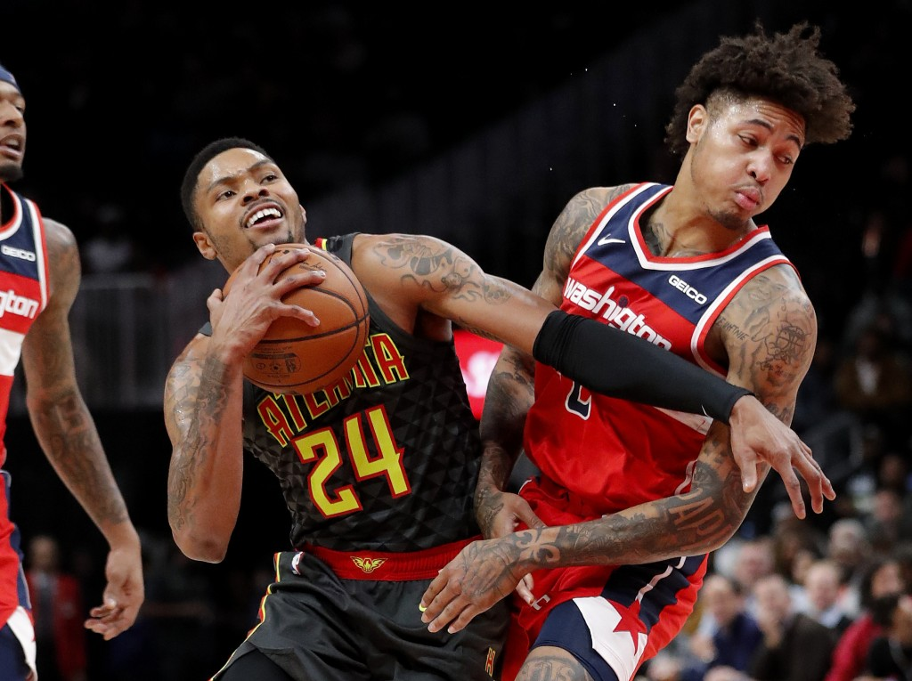Atlanta Hawks guard Kent Bazemore (24) is fouled by Washington Wizards forward Kelly Oubre Jr. (12) during the first half of an NBA basketball game We
