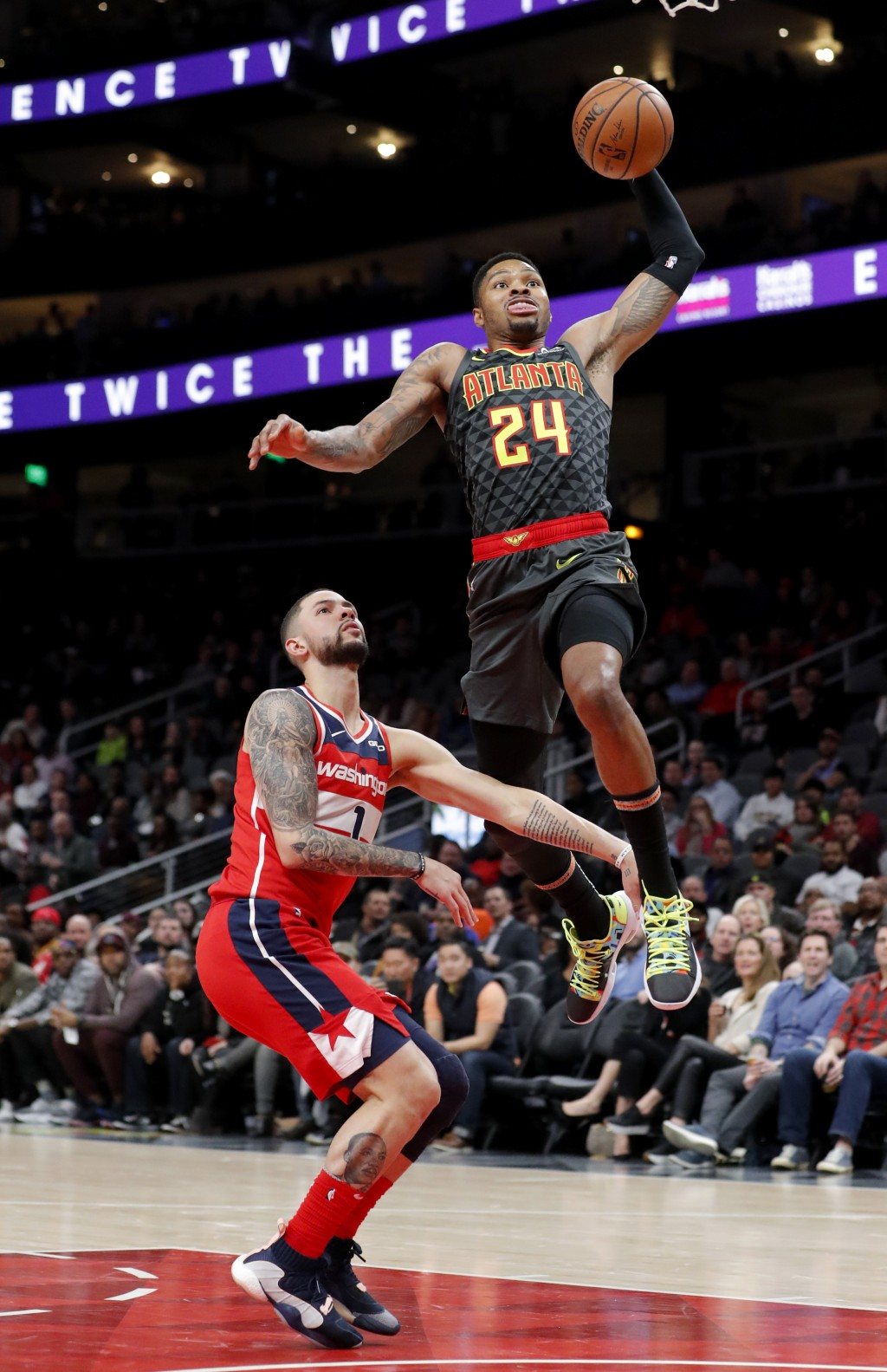 Atlanta Hawks guard Kent Bazemore (24) goes over Washington Wizards guard Austin Rivers (1) for a dunk during the first half of an NBA basketball game