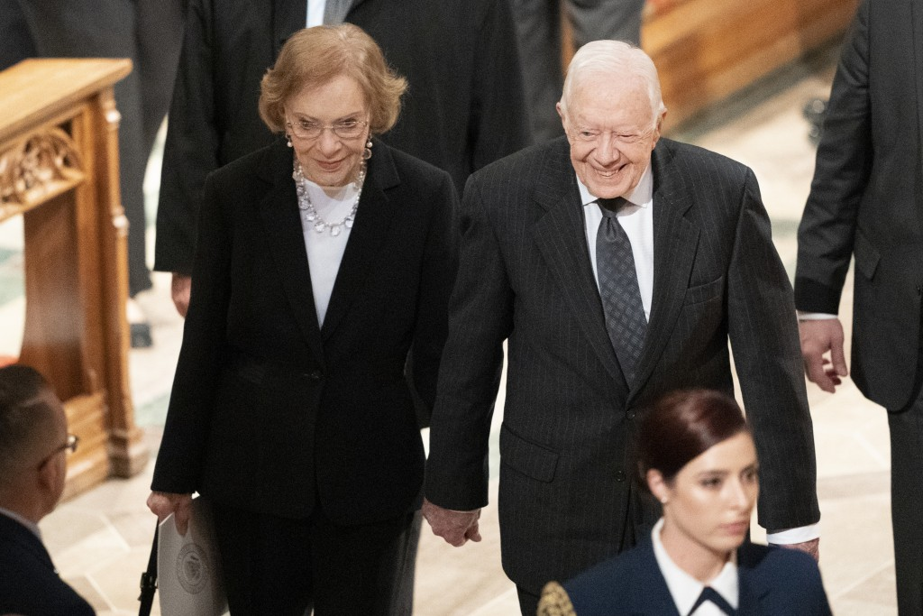 Former President Jimmy Carter, and Rosalynn Carter hold hands as they walk from a State Funeral for former President George H.W. Bush at the National