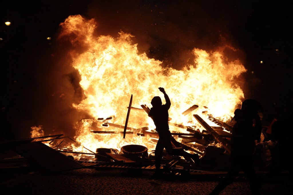 FILE - In this Nov. 24, 2018 file photo, a demonstrator throws debris at a burning barricade while protesting with others against the rising of the fu