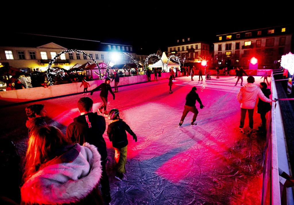 In this Tuesday, Dec. 4, 2018 photo people use an ice rink at the traditional Christmas market in Heidelberg, Germany. The Christmas market In the Old