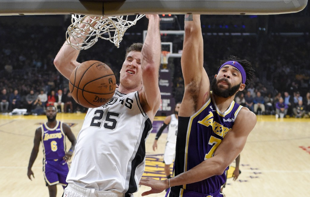 San Antonio Spurs center Jakob Poeltl, left, of Austria, dunks as Los Angeles Lakers center JaVale McGee defends during the first half of an NBA baske