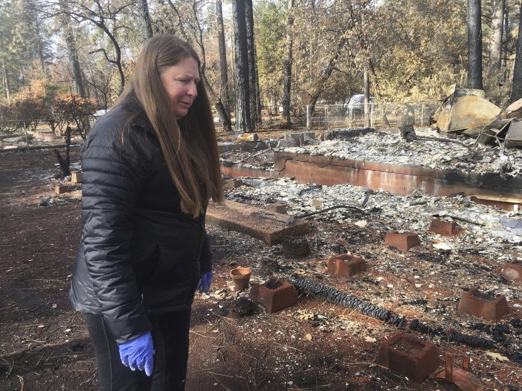 Resident Linda Matthews returns to her home destroyed in the Camp Fire in Paradise, Calif., Wednesday, Dec. 5, 2018. Hundreds of residents were finall