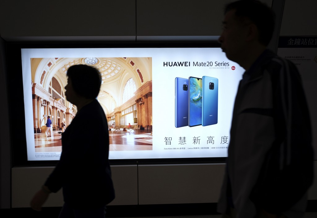 People walk past an advertisement for Huawei at a subway station in Hong Kong Thursday, Dec. 5, 2018. Canadian authorities said Wednesday that they ha...