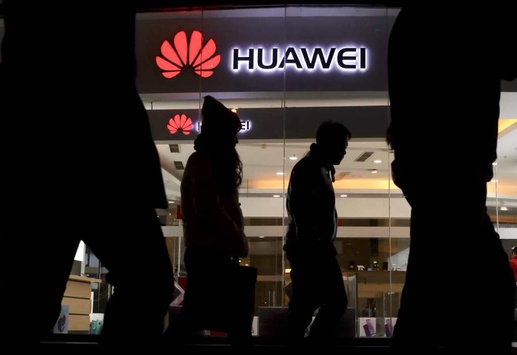 Pedestrians walk past a Huawei retail shop in Beijing Thursday, Dec. 6, 2018. China on Thursday demanded Canada release a Huawei Technologies executiv