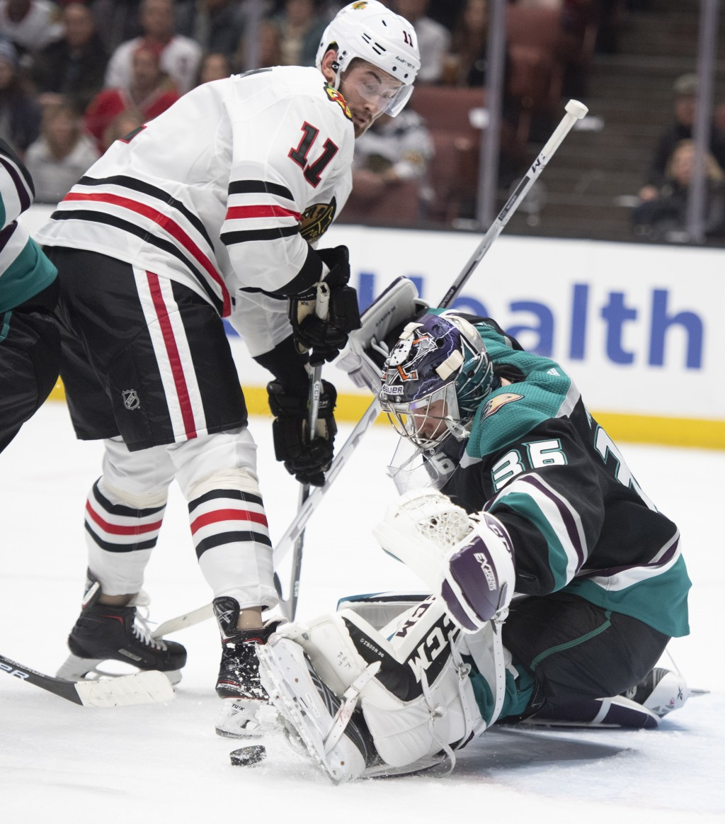 Anaheim Ducks goaltender John Gibson, right, blocks a shot in front of Chicago Blackhawks left wing Brendan Perlini in the first period of an NHL hock