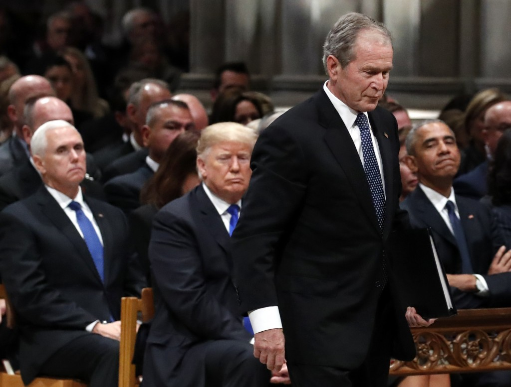 Former President George W. Bush walks past President Donald Trump and former President Barack Obama to speak a State Funeral for President George H.W.