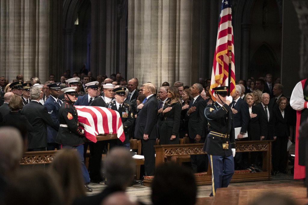 The flag-draped casket of former President George H.W. Bush is carried by a military honor guard past former President George W. Bush, left side, Pres