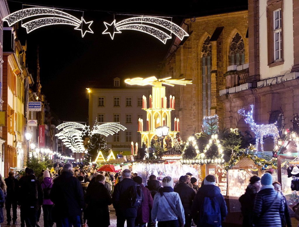 In this Tuesday, Dec. 4, 2018 photo people pay a visit to the traditional Christmas market in Heidelberg, Germany. The Christmas market In the Old Tow