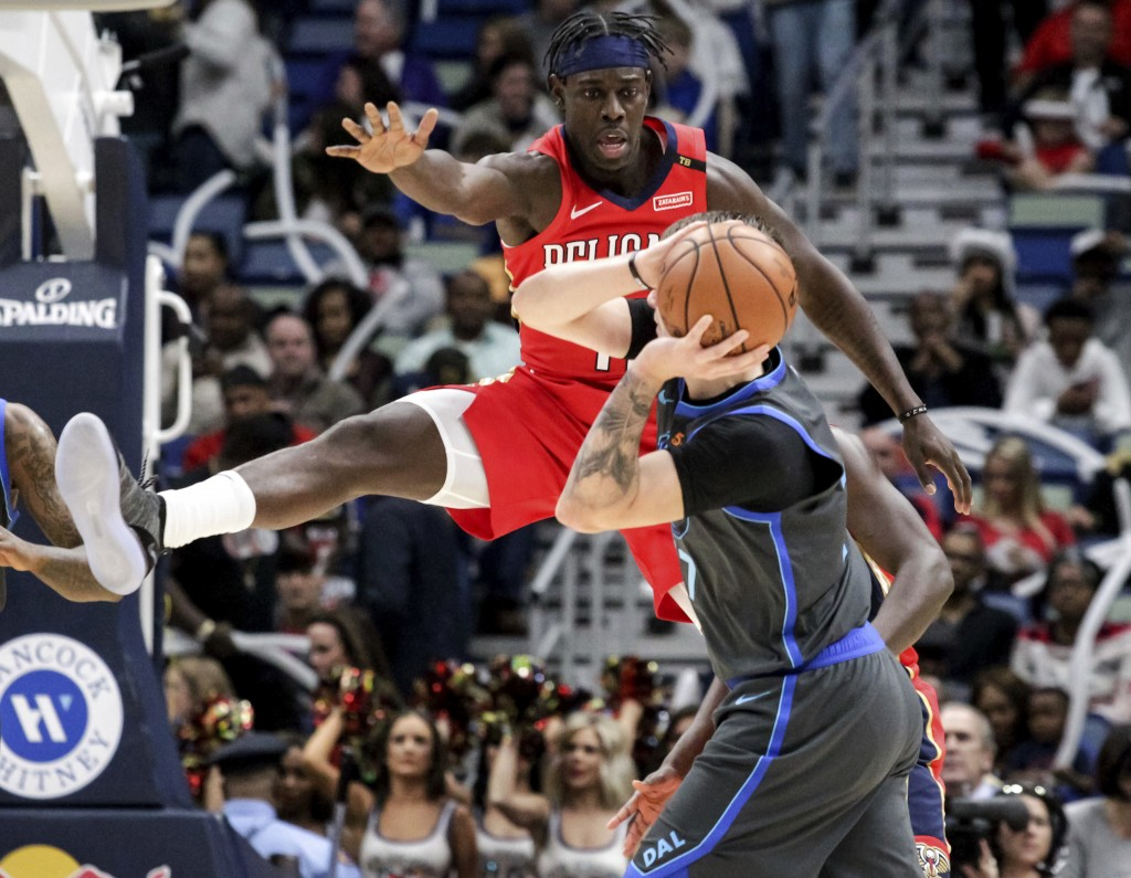 New Orleans Pelicans guard Jrue Holiday (11) guards Dallas Mavericks forward Luka Doncic (77) in the first half of an NBA basketball game in New Orlea