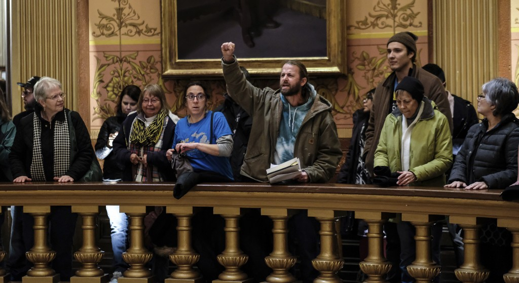 In this Tuesday, Dec. 4, 2018, photo, people take turns speaking to protest the lame duck legislation in the Capitol Rotunda in Lansing, Mich. The inc