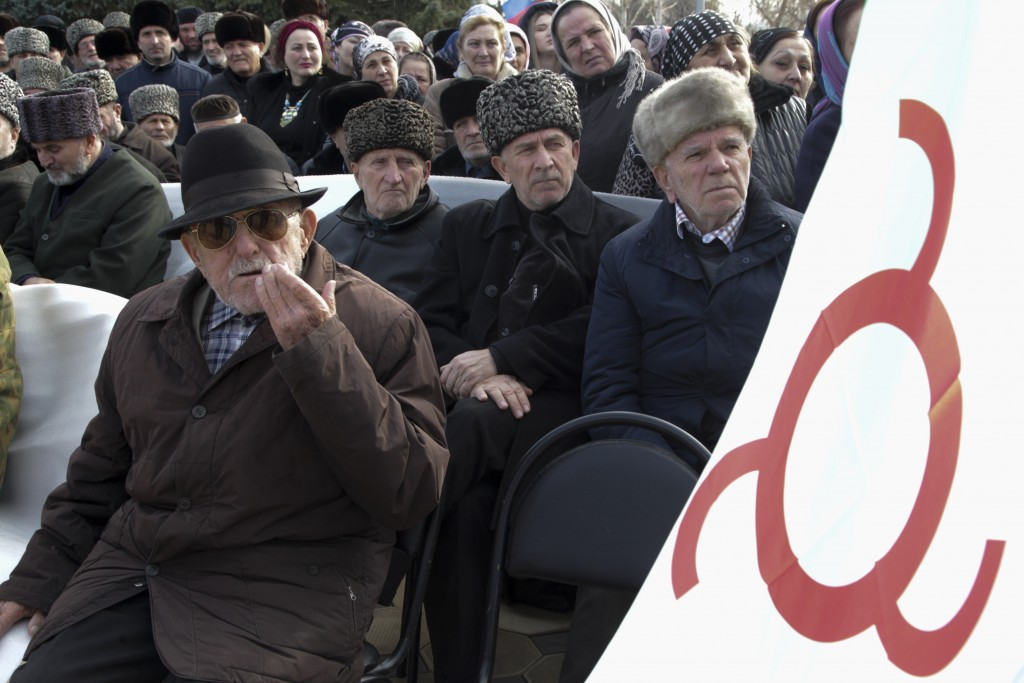 FILE - In this Tuesday, Nov. 27, 2018 file photo, local people with a Ingushetia region flag attend a protest against the new land swap deal agreed by