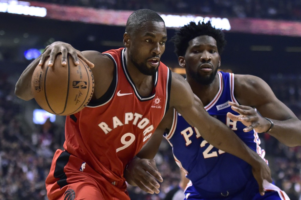 Toronto Raptors forward Serge Ibaka (9) controls the ball as Philadelphia 76ers center Joel Embiid (21) defends during the first half of an NBA basket
