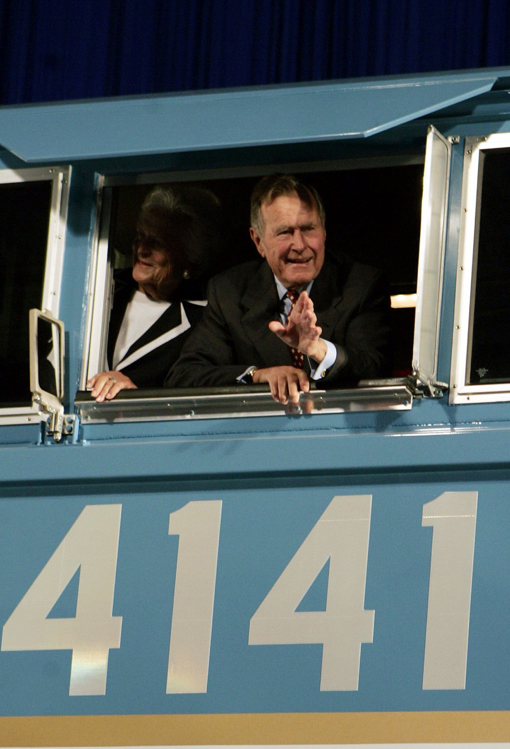 FILE - In this Oct. 18, 2005, file photo, former President George H.W. Bush and his wife Barbara wave out the window of a new locomotive numbered 4141