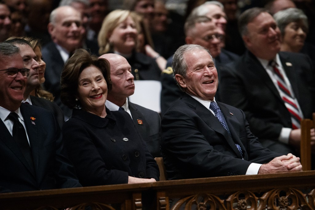 Jeb Bush, Laura Bush, and former President George W. Bush share a laugh as a story is told about former President George H.W. Bush during a State Fune
