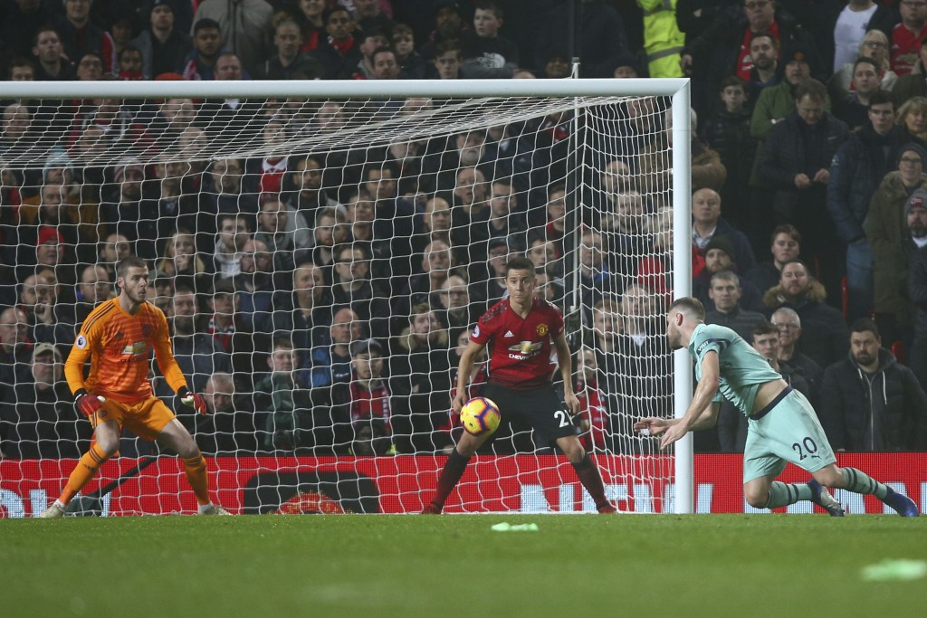 Arsenal's Shkodran Mustafi, right, heads the ball to score his side's first goal passing Manchester United's goalkeeper David de Gea, left, during the