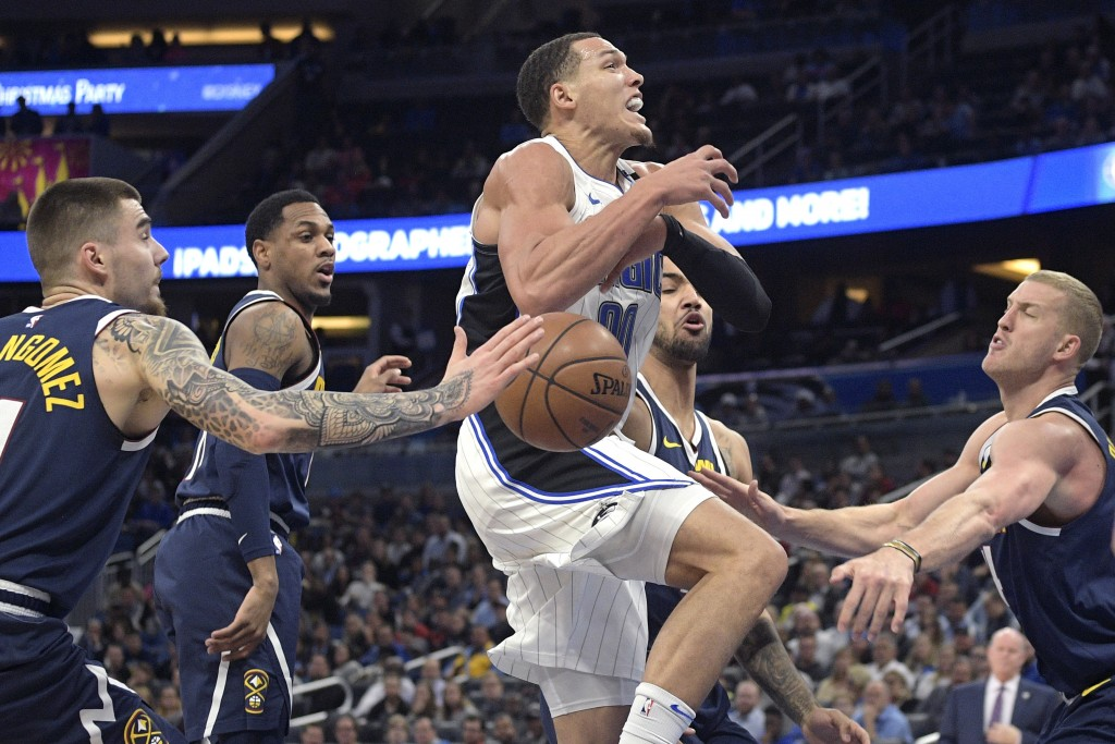 Orlando Magic forward Aaron Gordon (00) is stripped of the ball while going up for a shot between Denver Nuggets forward Juan Hernangomez, left, guard