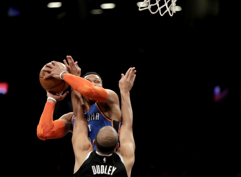 Oklahoma City Thunder guard Russell Westbrook, back, goes up for a shot against Brooklyn Nets forward Jared Dudley during the first half of an NBA bas
