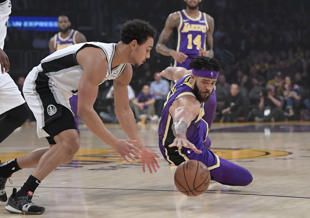San Antonio Spurs guard Bryn Forbes, left, and Los Angeles Lakers center JaVale McGee go after a loose ball during the first half of an NBA basketball
