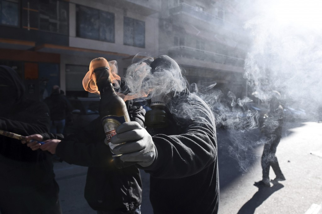 A hooded youth prepares to throw a petrol bomb at riot police in the northern Greek city of Thessaloniki, on Thursday, Dec. 6, 2018 during a rally com