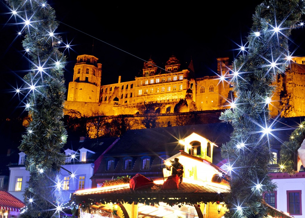 In this Tuesday, Dec. 4, 2018 photo lights shine in front of the castle at the traditional Christmas market in Heidelberg, Germany. The Christmas mark