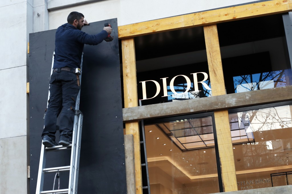 FILE - In this Friday, Nov. 30, 2018 file picture, a worker reinforces store windows on the famed Champs Elysees avenue to prepare for an expected pro