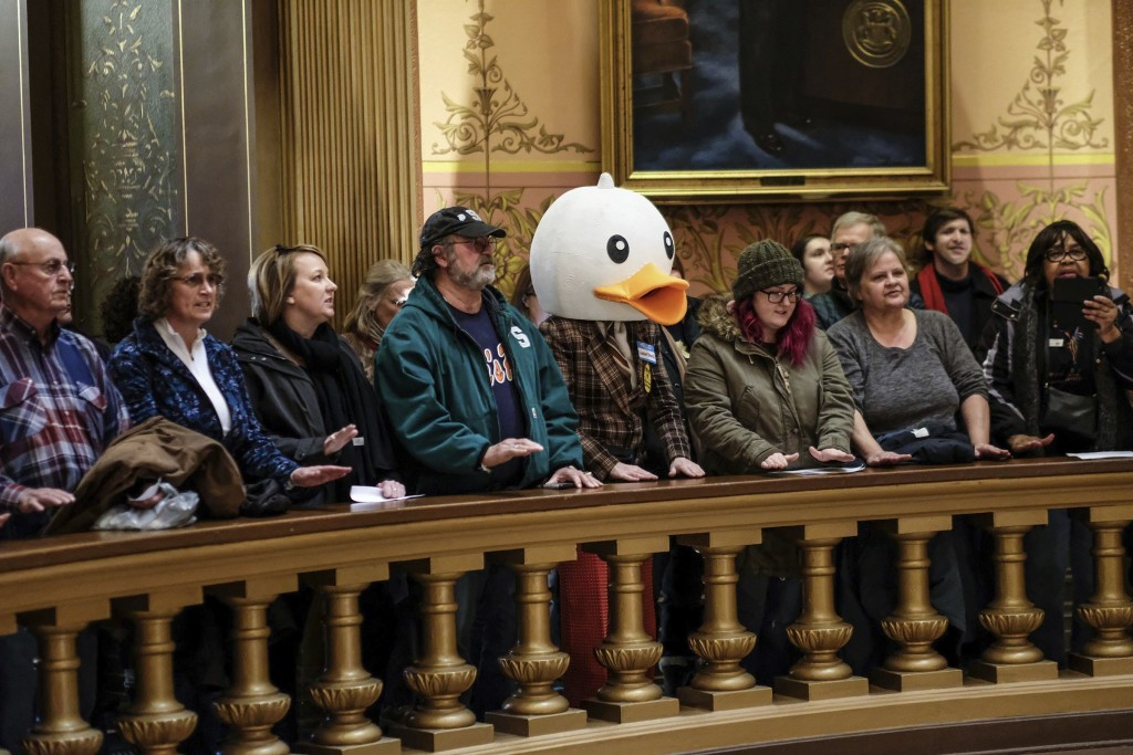 In this Tuesday, Dec. 4, 2018, photo, people gather to protest at the Capitol Rotunda in Lansing, Mich. The incoming Democratic governor of Wisconsin