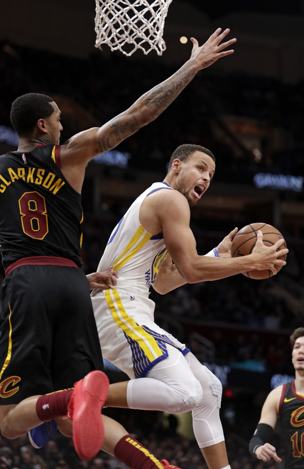 Golden State Warriors' Stephen Curry, right, drives to the basket against Cleveland Cavaliers' Jordan Clarkson in the second half of an NBA basketball