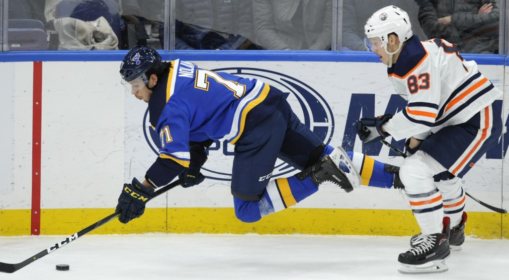 St. Louis Blues' Jordan Nolan (71) dives for the puck in front of Edmonton Oilers' Matt Benning (83) during the second period of an NHL hockey game, W