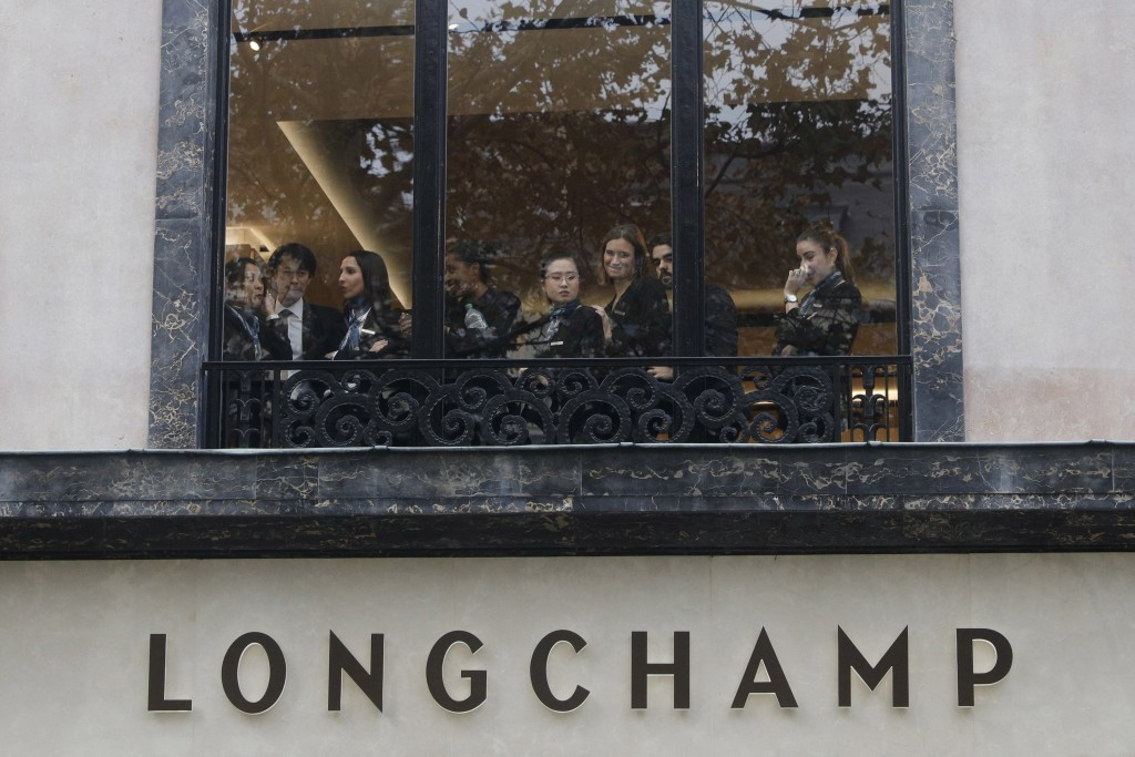 FILE - In this Saturday, Nov. 24, 2018 file picture, employees, stranded in a store on the famed Champs-Elysees avenue, watch demonstrators, known as
