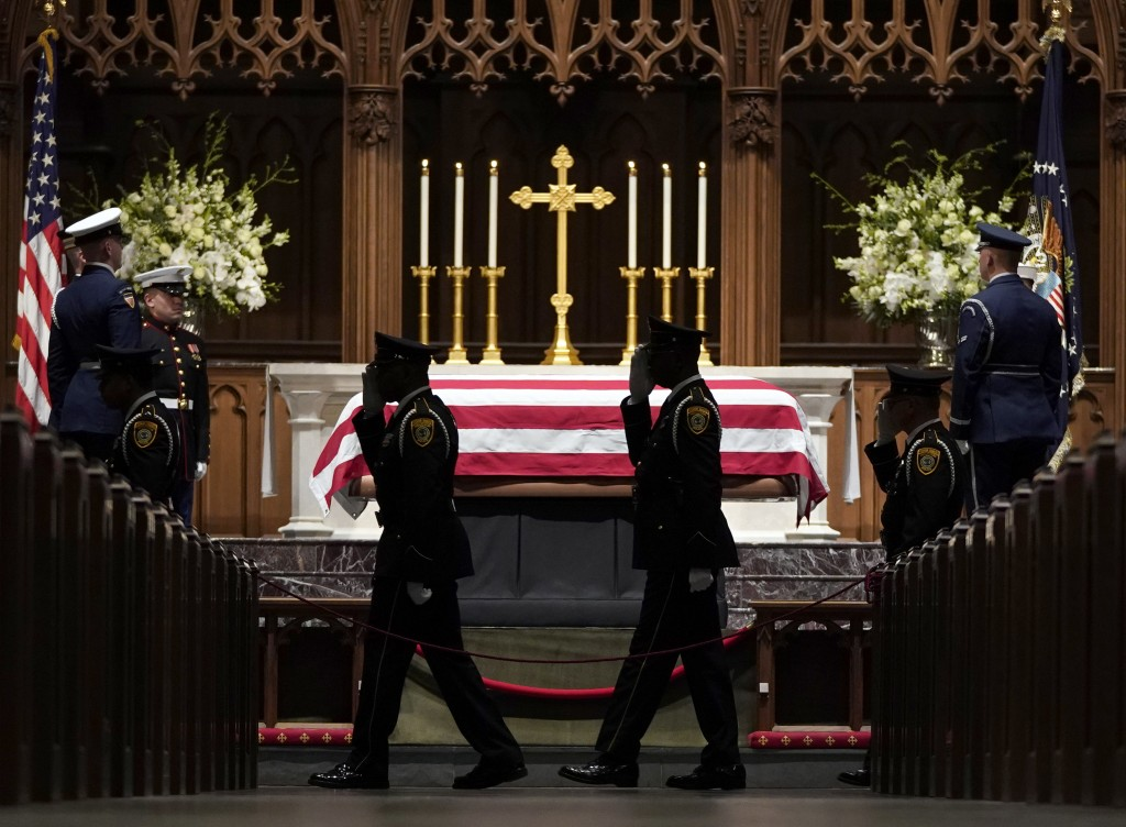 Military members salute as they pay their respects as former President George H.W. Bush lies in repose at St. Martin's Episcopal Church Wednesday, Dec