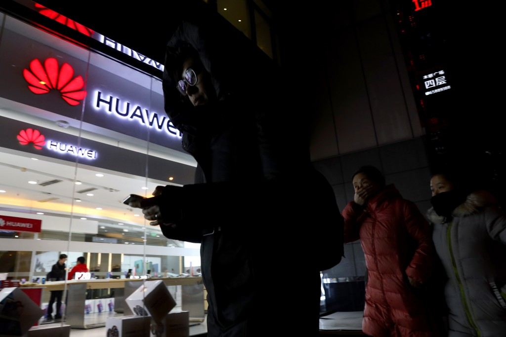 People walk past a Huawei retail shop in Beijing Thursday Dec. 6 2018. China on Thursday demanded Canada release a Huawei Technologies executive who