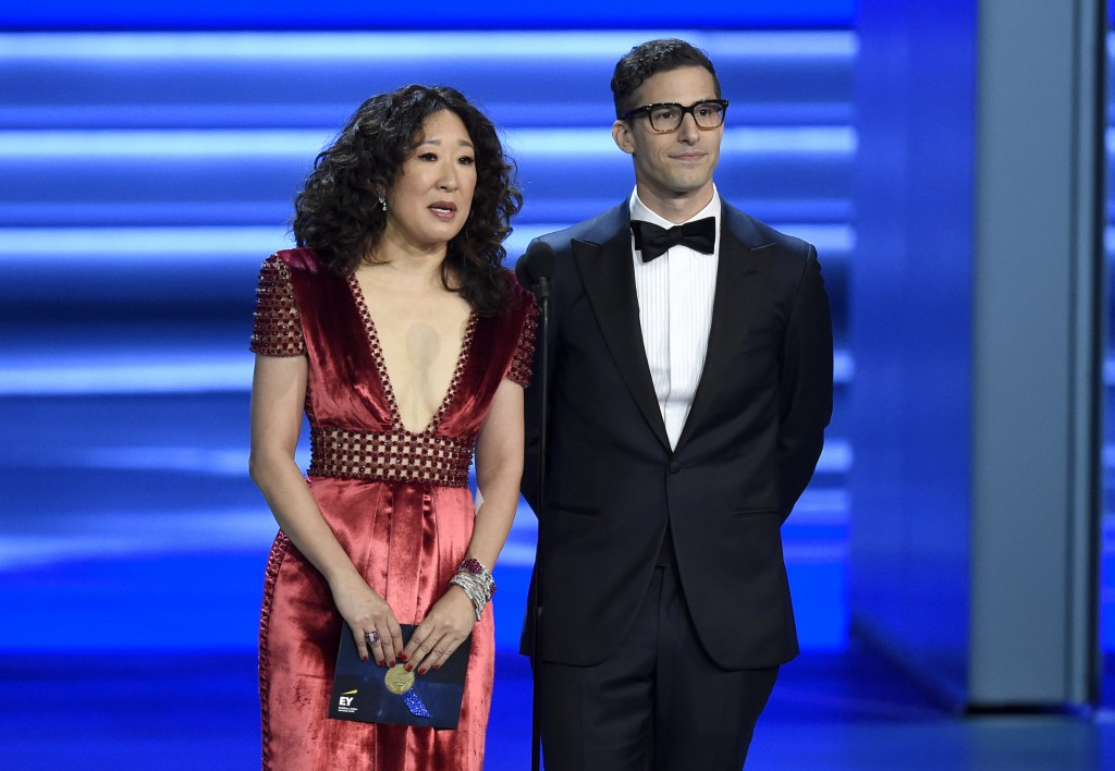 FILE - In this Sept. 17, 2018 file photo, Sandra Oh, left, and Andy Samberg present an award at the 70th Primetime Emmy Awards in Los Angeles. Oh and