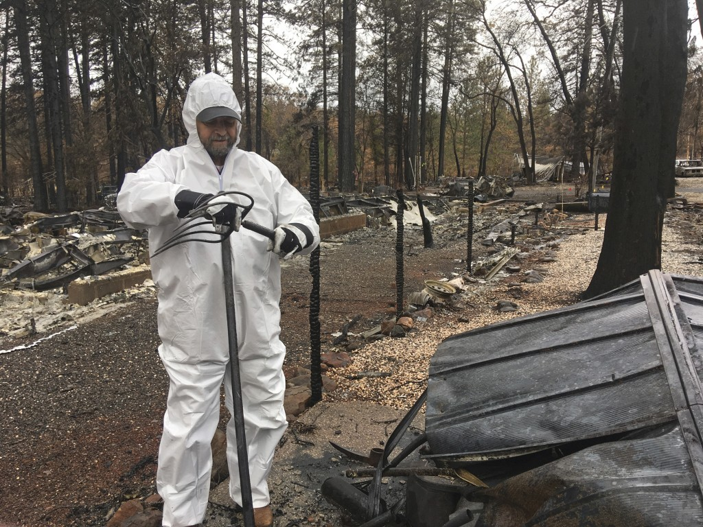 Jerry McLean, wearing a hazmat suit, looks over tools he found in a burned shed at his home Wednesday, Dec. 5, 2018, in Paradise Calif. Some residents