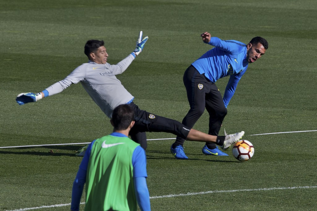 Boca Junior's Carlos Tevez, right, is challenged by goalkeeper Esteban Andrade during a training session in Madrid, Spain, Thursday, Dec. 6, 2018. The