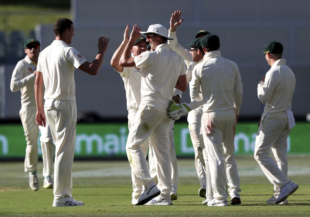 Australia's Pat Cummins, centre, is congratulated by teammates after he ran out India's Cheteshwar Pujara during the first cricket test between Austra